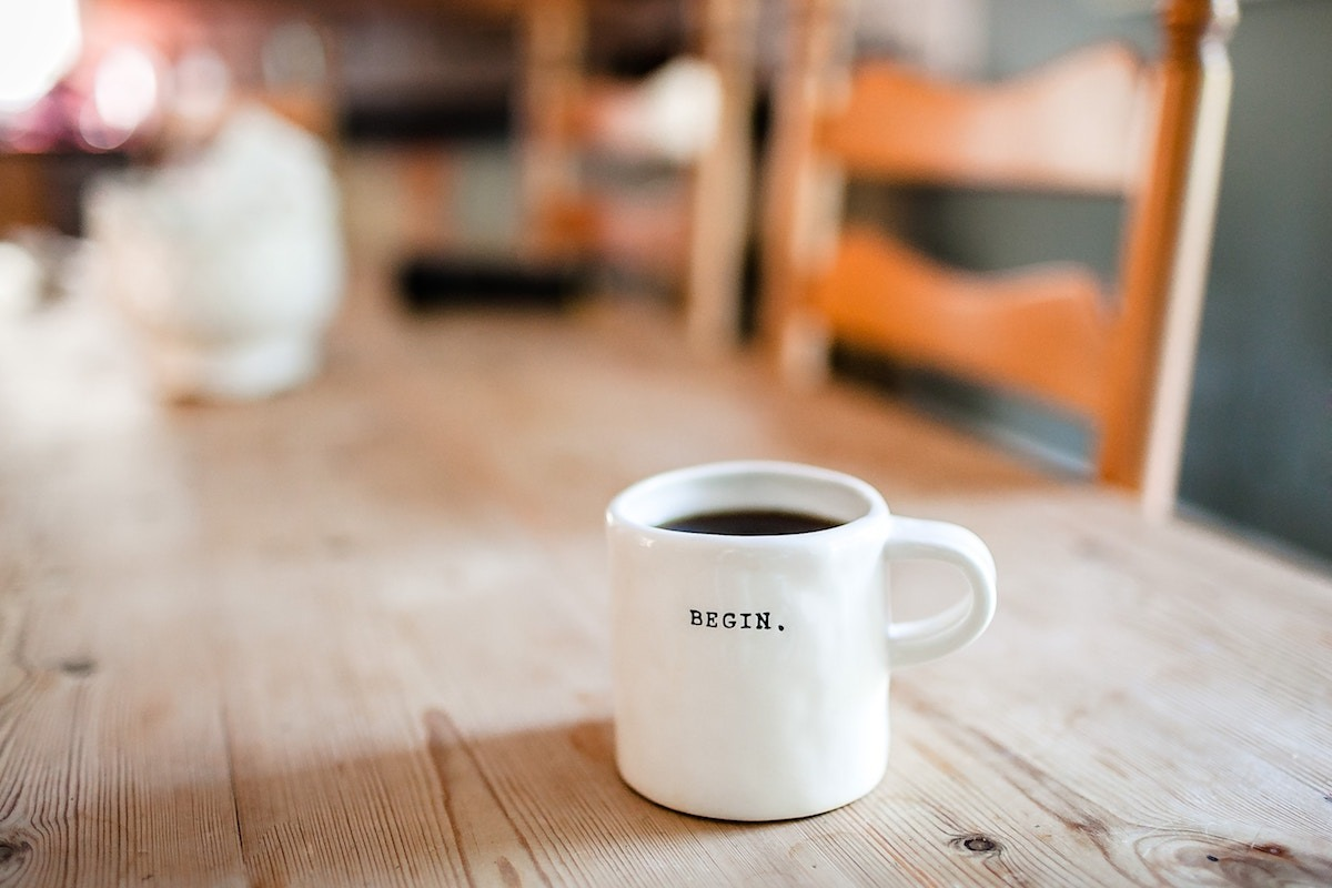 Coffee mug saying 'Begin' on table