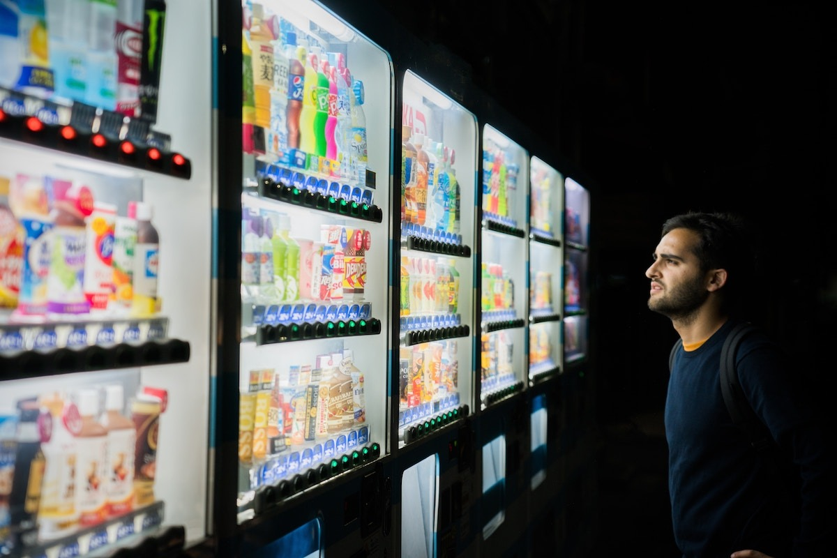 Man looking at candy vending machines